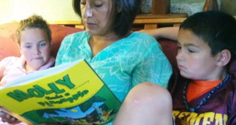 Parent reading Molly the Monkey to children